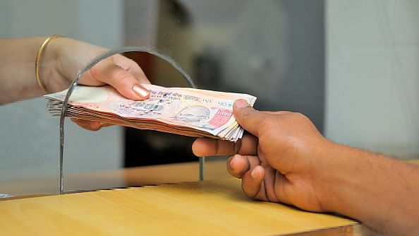 Cash transfer at a counter for stock on banking. The government has given a big boost to e-payments.