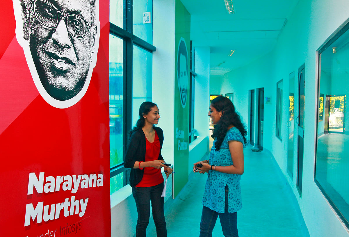 Employees talk as they stand next to flex board poster of Infosys founder Narayana Murthy at the Start-up Village in Kinfra High Tech Park in Kochi. The Indian IT sector, led by behemoths such as TCS, Infosys, HCL Systems and Wipro, among dozens of others, is expecting to return to the high growth path from this year.