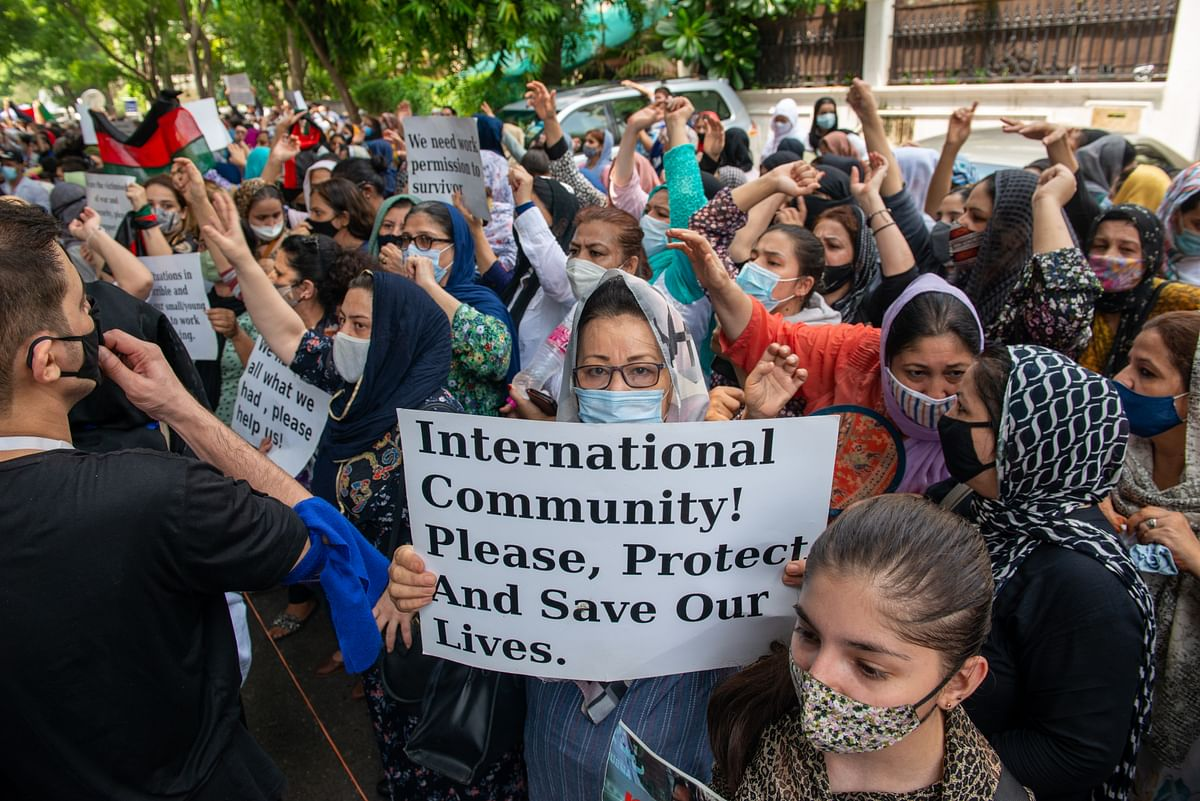 Afghan refugee women  hold placards in front of the UNHCR office at Vasant Vihar, New Delhi. The G7, in a virtual summit, has insisted that the current Afghan administration have to guarantee, through August 31 and beyond, safe passage for those who want to come out.