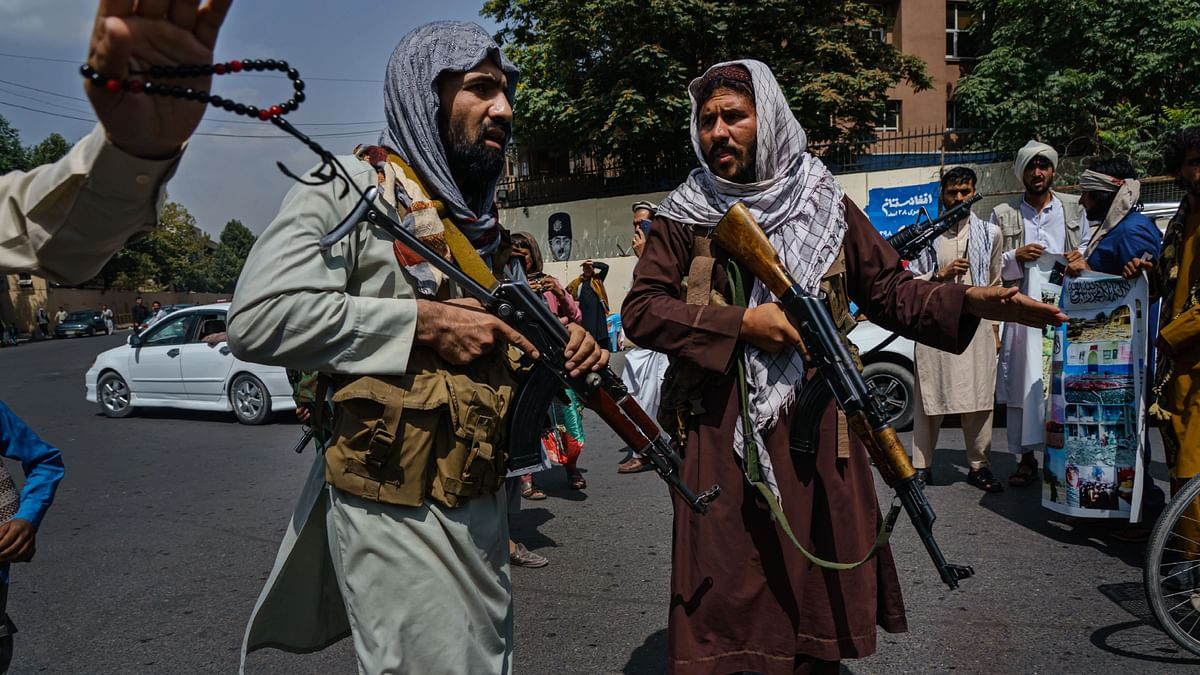 Taliban fighters mobilize to control a crowd rallying to raise the national flag of the Islamic Republic of Afghanistan. Raab stressed that the UK and India need to partner together to find a solution to the Afghan problem, 'one of its gravest foreign policy crises in recent times'