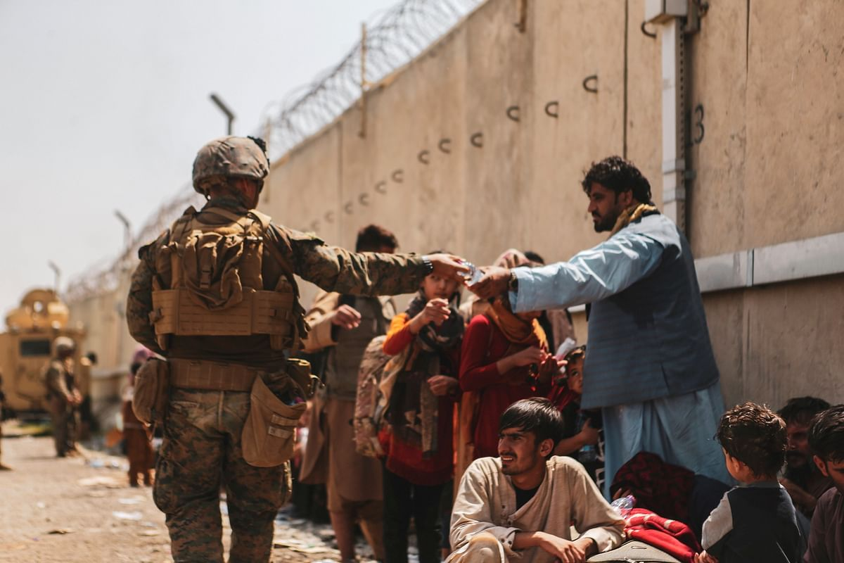 A US Marine passes out water to evacuees during an evacuation at Hamid Karzai International Airport, Kabul, Afghanistan. Putting to use its new-found leadership stature in the world, India would have to make a pitch so that other powerful nations can see the potential threat that China poses through the Afghanistan crisis.