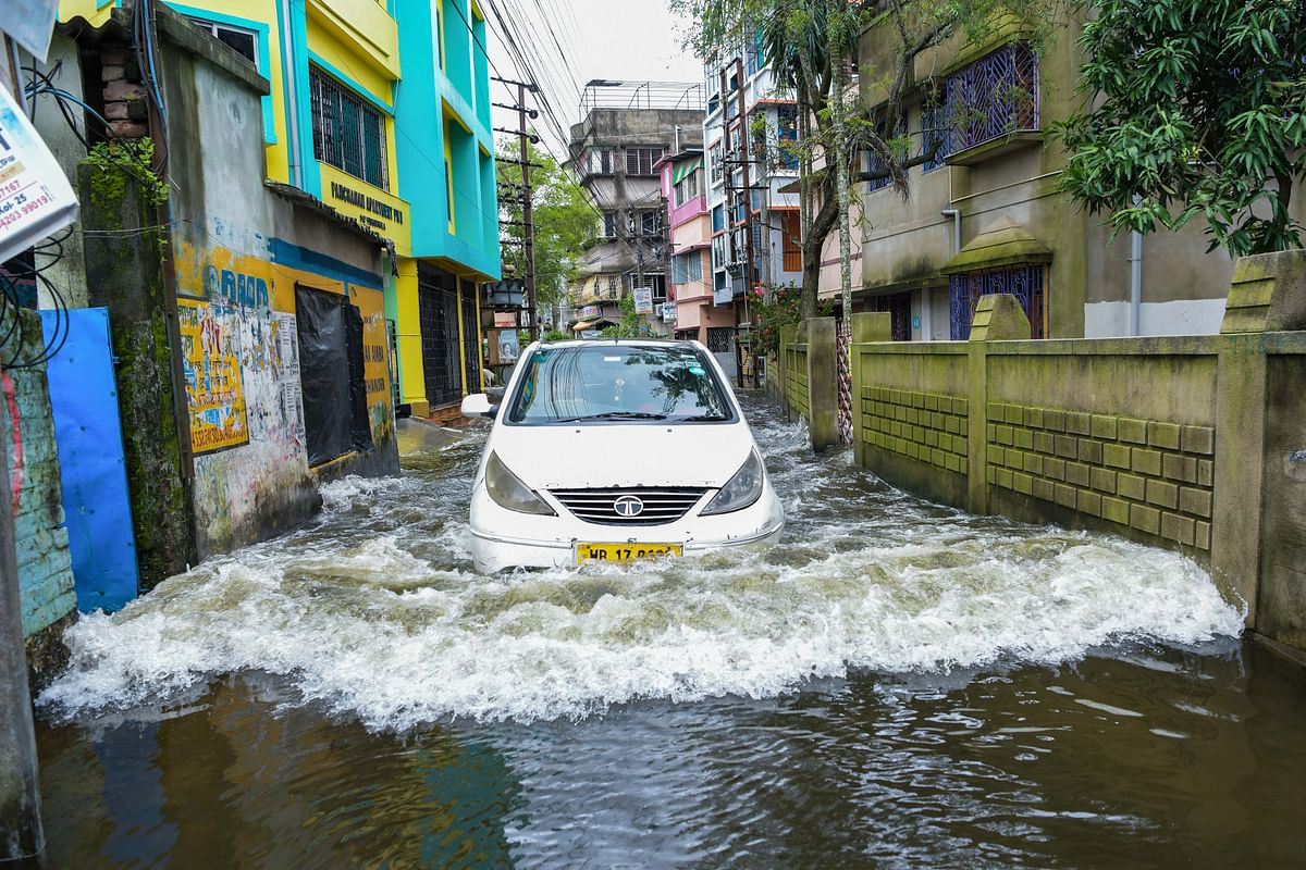 A car drives through a waterlogged road during the aftermath of a heavy monsoon downpour in India. Some parts of India received heavy rains caused by a low-pressure system over Bangladesh and West Bengal. In combating climate change, India is taking action on renewables, clean technology and infrastructure.