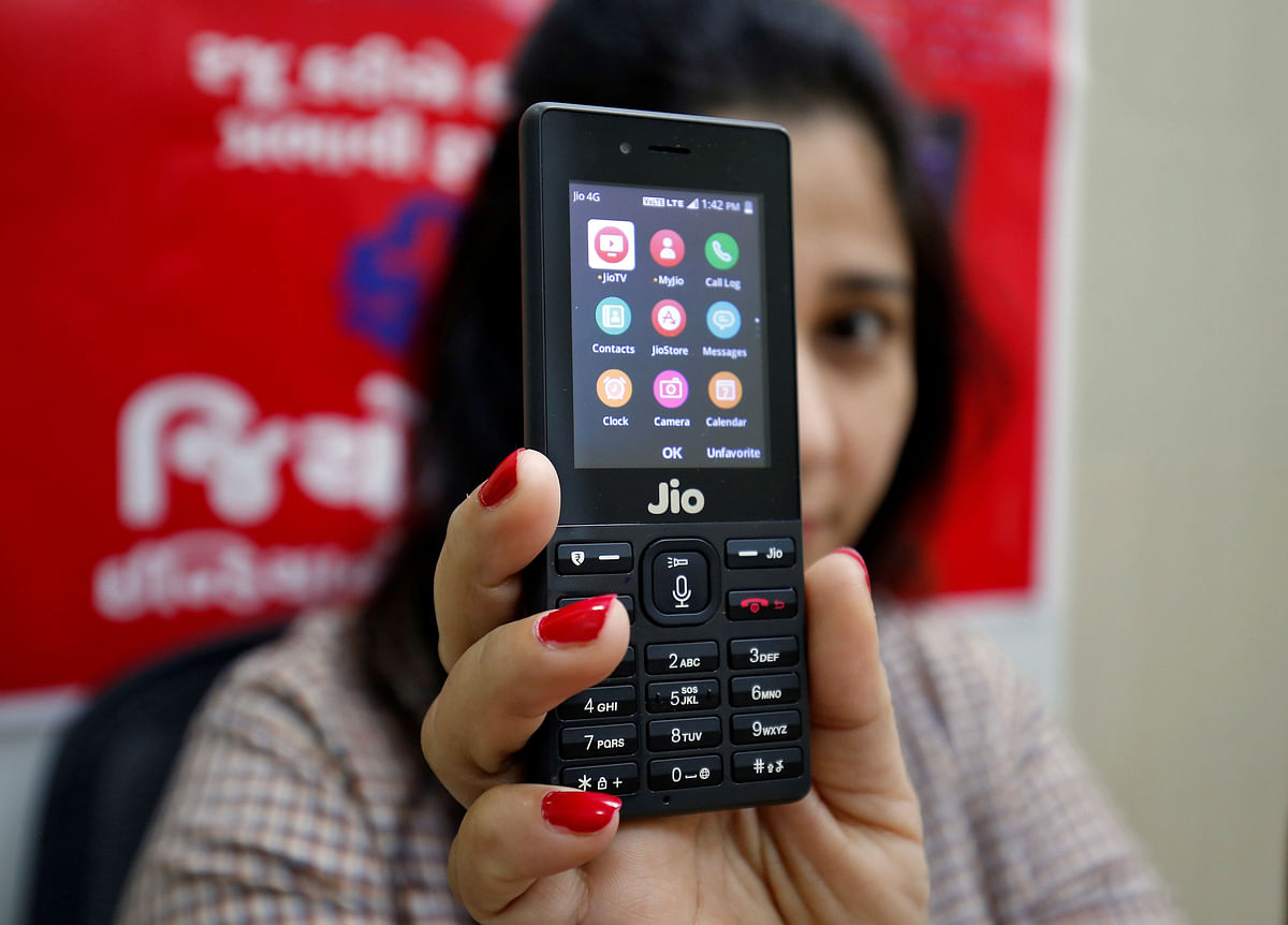 Dialling up the competition. A salesperson displays the JioPhone as she poses for a photograph at a store of Reliance Industries' Jio telecoms unit, near Ahmedabad.