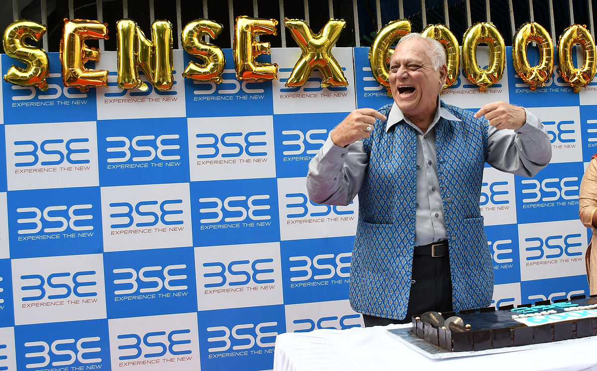 """A man celebrates outside the Bombay Stock Exchange (BSE) in Mumbai. Sensex crossed 60,000 level for the first time. According to the RBI Governor, """"The worst of the second wave is behind us, and substantial pickup in COVID-19 vaccination, giving greater confidence to open up and normalize economic activity."""""""