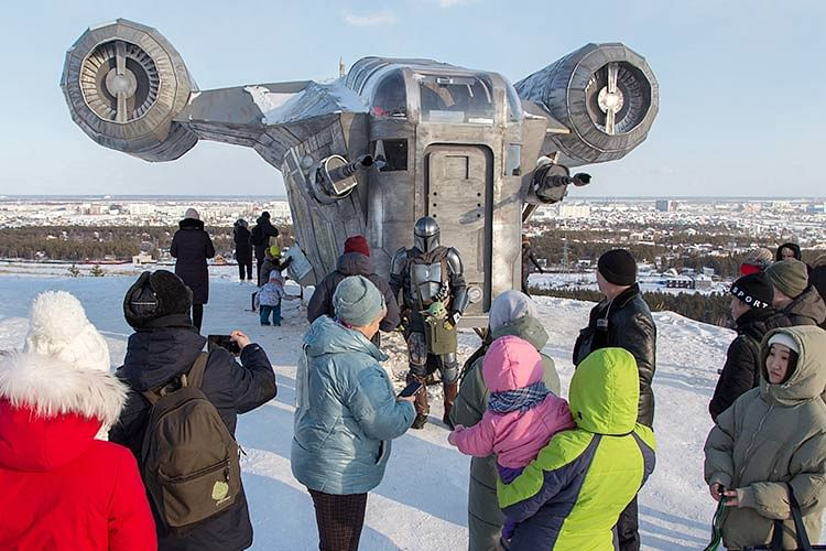 "People stand by a giant replica of the Razor Crest, a a gunship from the StarWars spinoff series ""The Mandalorian."""