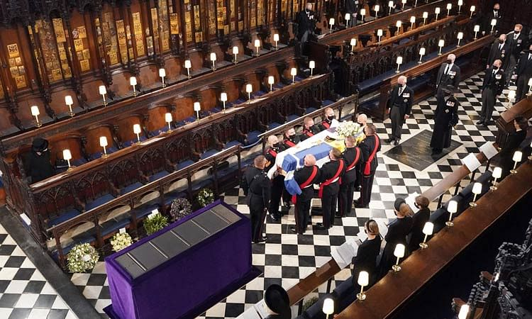 Queen Elizabeth (L) watches as pallbearers carry the coffin of Prince Philip.