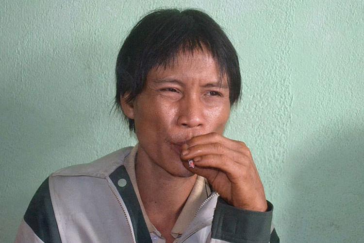 Ho Van Lang smokes at his home.