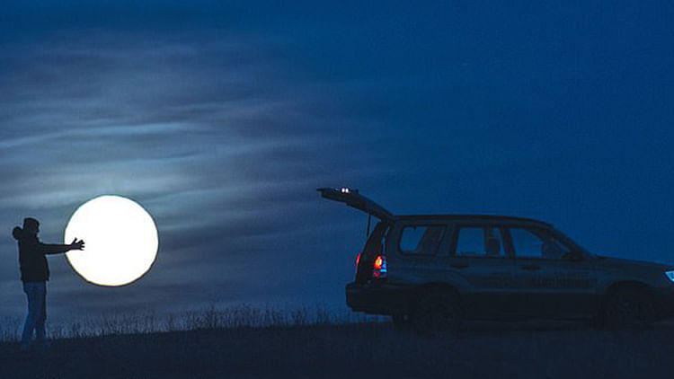 Photographer Cris Froese captures moon being loaded into car's boot, names it 'Theft of the Moon'