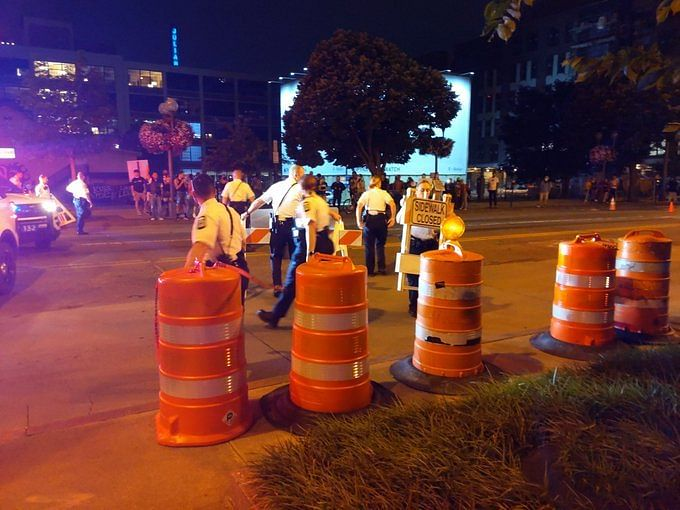 Six police officers remove traffic cones and signs from the intersection at Main and High Street. Officers also removed traffic cones from Rich and High Street before returning to their vehicles.