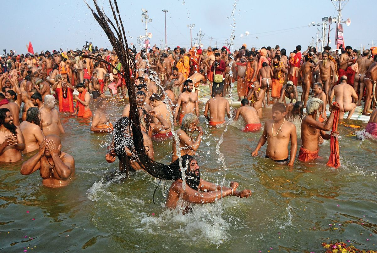 Indian naked sadhus jump into the waters of the holy Sangam during the auspicious bathing day of 'Mauni Amavasya' at the Kumbh Mela in Allahabad on February 4, 2019