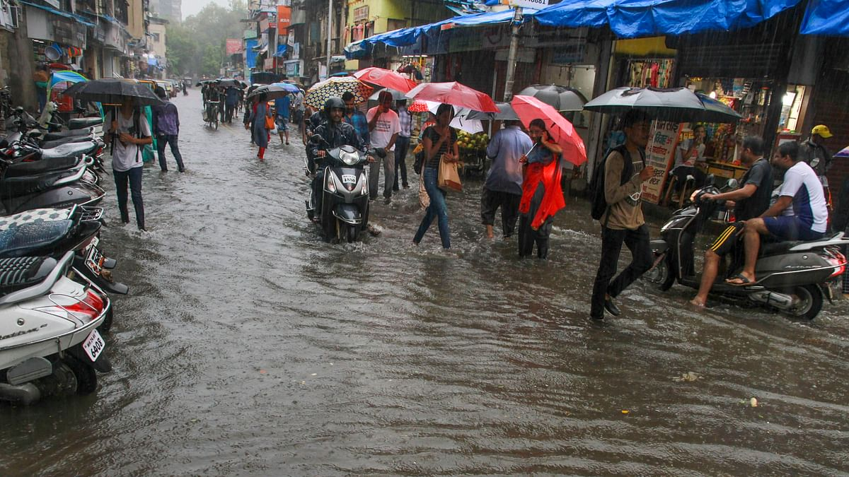 Commuters wade through a water-logged street after heavy rainfall, in Thane