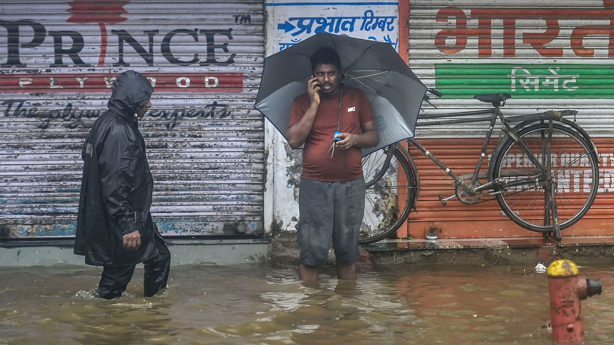 Pedestrians wade through a waterlogged street during monsoon rain, in Mumbai (PTI)