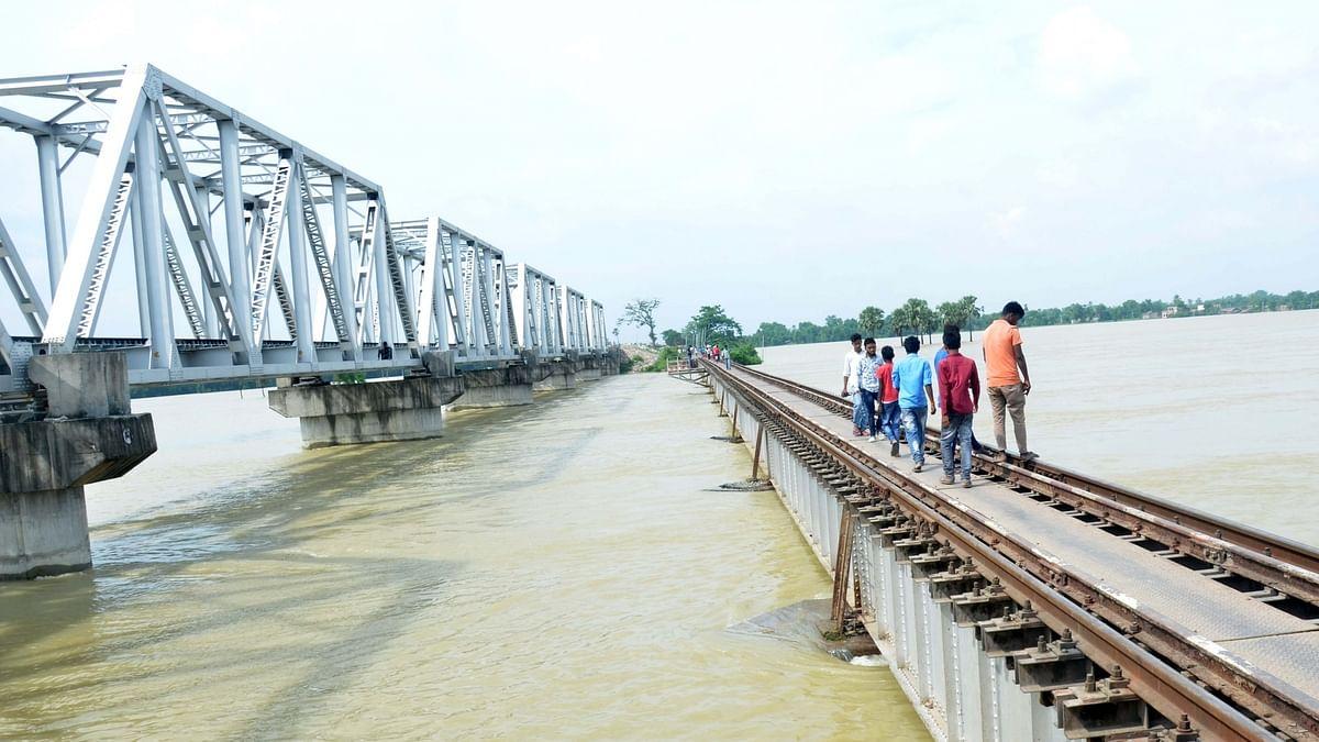 People walk across a railway bridge over the swollen Bagmati river following incessant monsoon rainfall, in Bihar's Darbhanga district