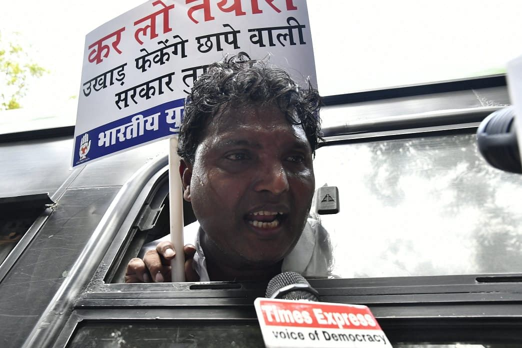 A Youth Congress activist being taken away in a police vehicle from the site of protest.