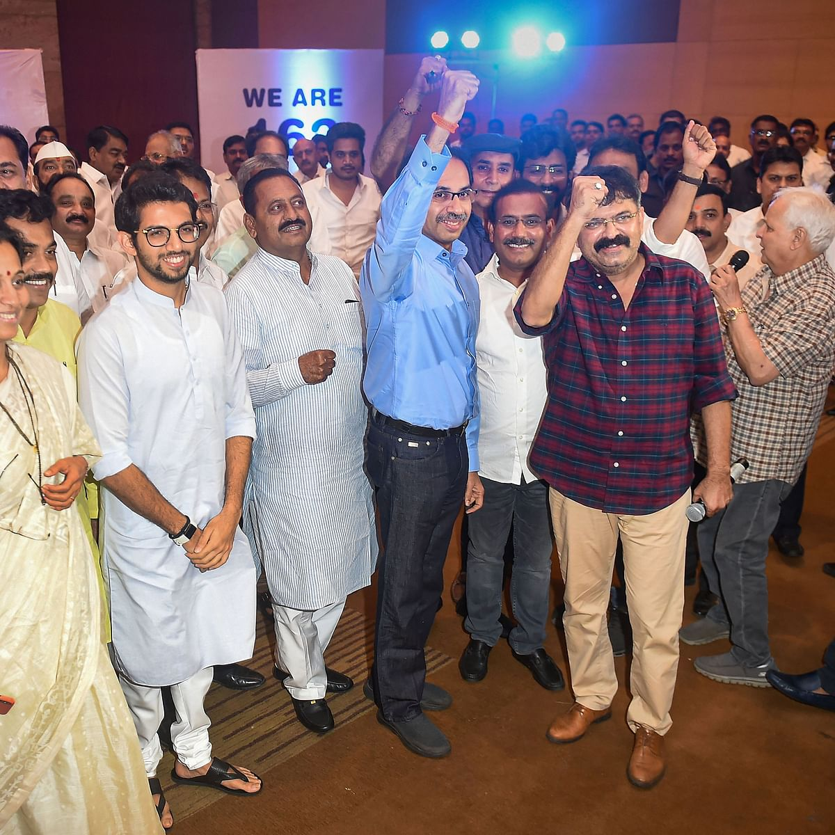 Sena chief Uddhav Thackeray  and NCP MLA Jitendra Awhad raise their fists as a sign of unity at the parade of NCP-Cong-Sena MLAs in Mumbai on Monday. NCP's Supriya Sule and Congress' Ashok Chavan are also in the frame.