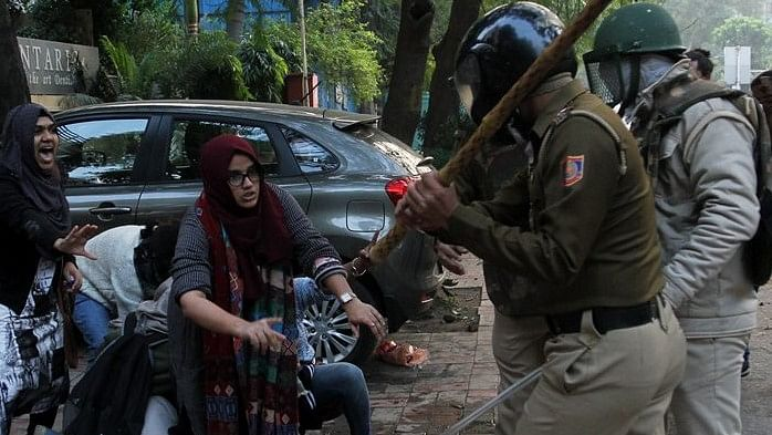 The two girls standing up to policemen who are brutally raining batons at one and all during anti-CAA protest (Photo Courtesy: social media)