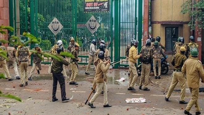 Police personnel outside Jamia Millia Islamia as students stage a protest against the Citizenship (Amendment) Act (PTI Photo)