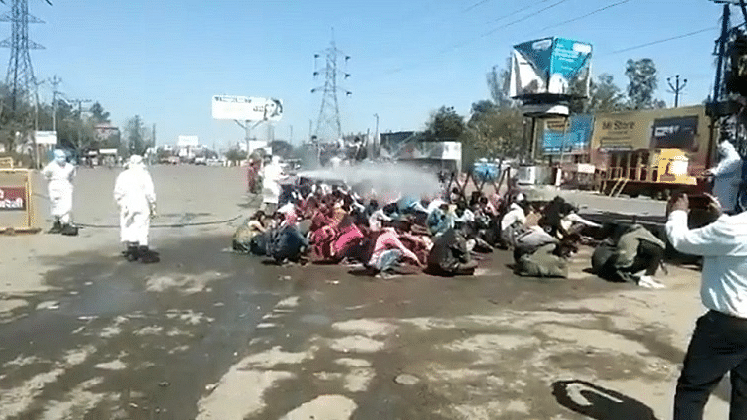 Migrant workers sprayed with disinfectant in Uttar Pradesh