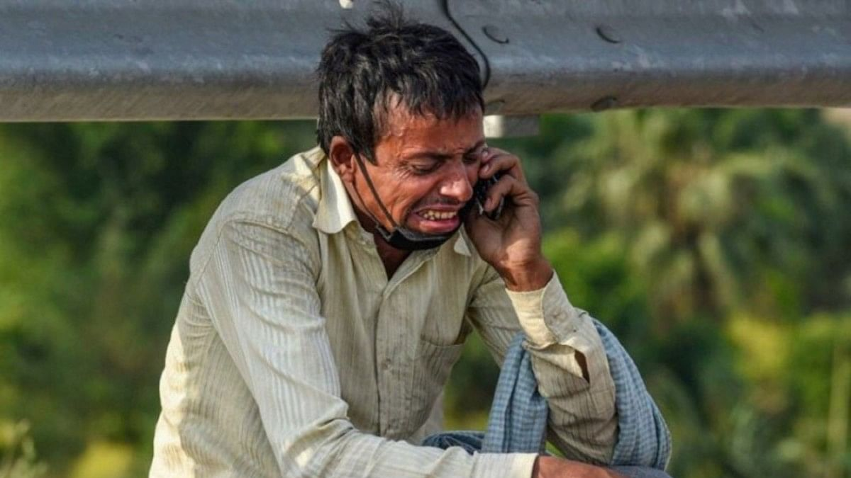 A migrant labourer crying while talking on the phone in Delhi