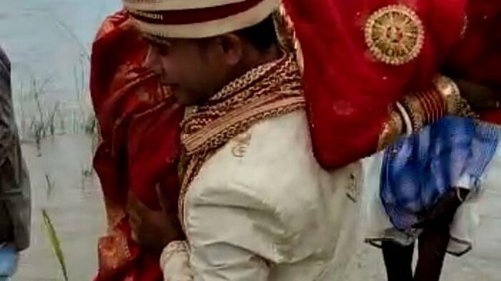 Bihar groom carries bride on shoulder across river