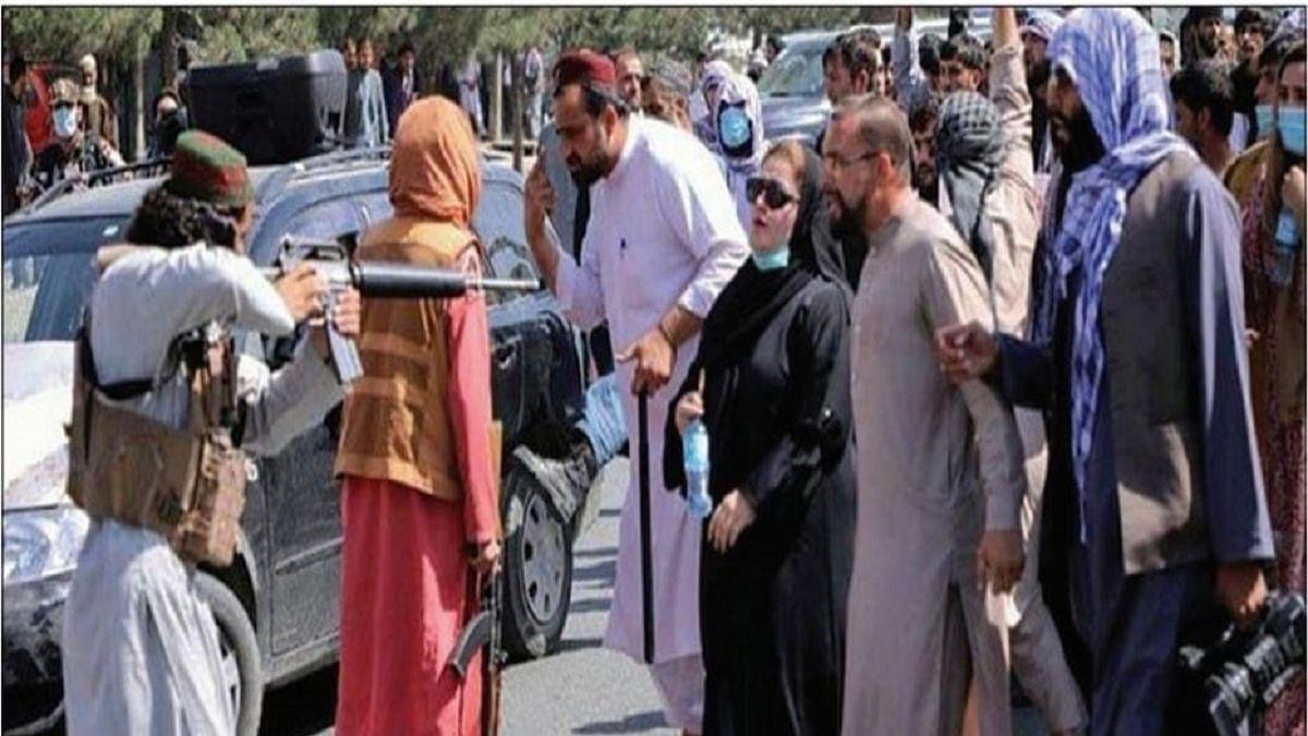 Taliban pointing a rifle at a woman