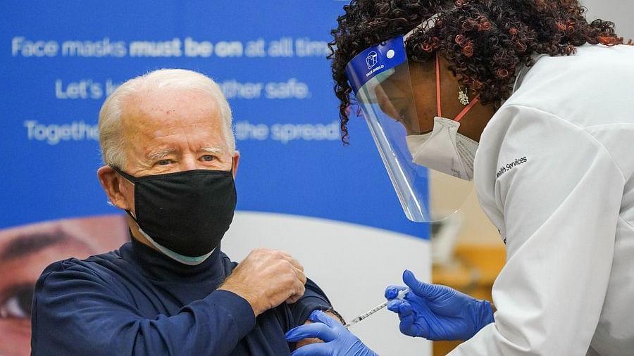 Joe Biden rolls up his sleeve to receive  jab