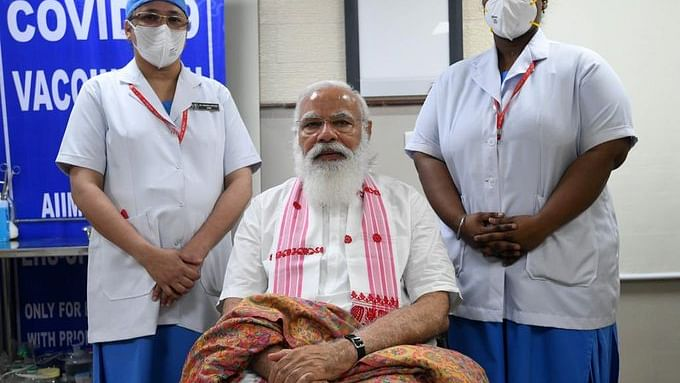 कोरोना वैक्सीन लेने में भी पीएम मोदी ने दिया चुनावी संदेश, केरल-पुडुचेरी की नर्स से असम का गमछा पहनकर लिया टीका