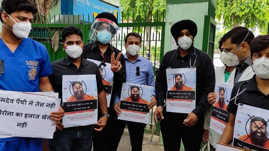 बाबा रामदेव के खिलाफ डॉक्टरों का विरोध प्रदर्शन, किसी ने गले में लगाया पोस्टर, किसी ने PPE में किया प्रोटेस्ट