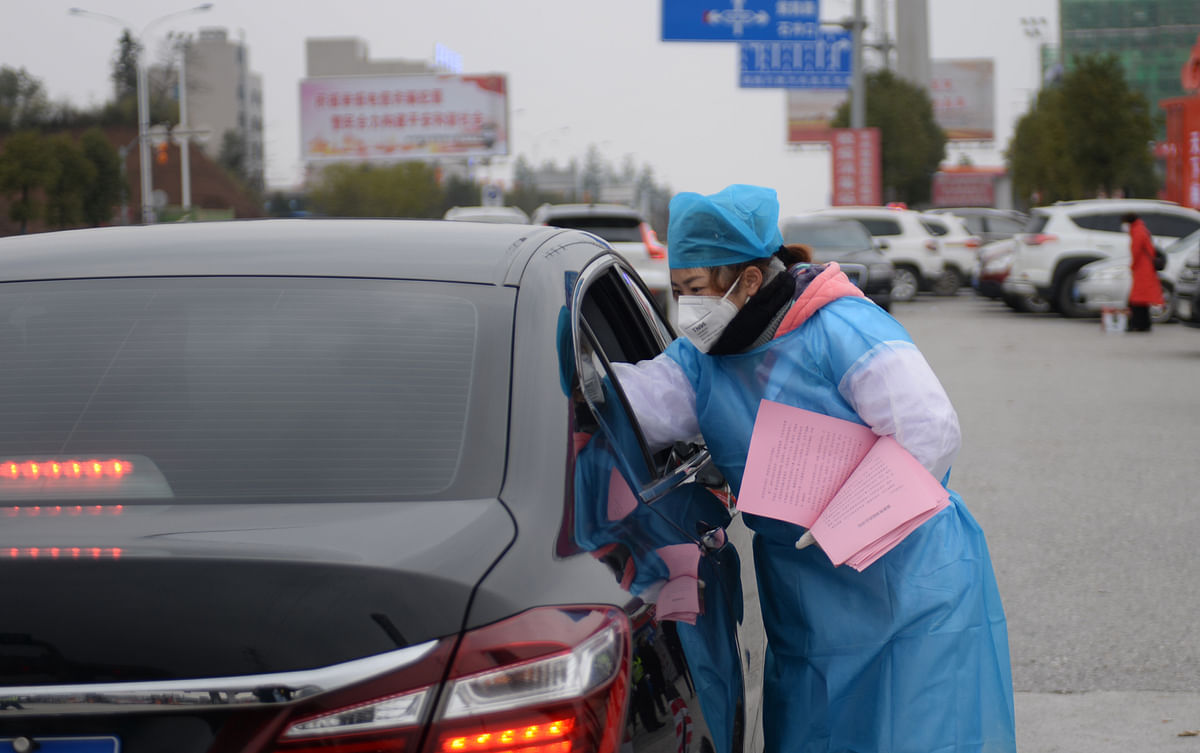 A worker distributes leaflets on the prevention and control of the novel coronavirus to drivers and passengers in Hunan province of China on January 27, 2020.