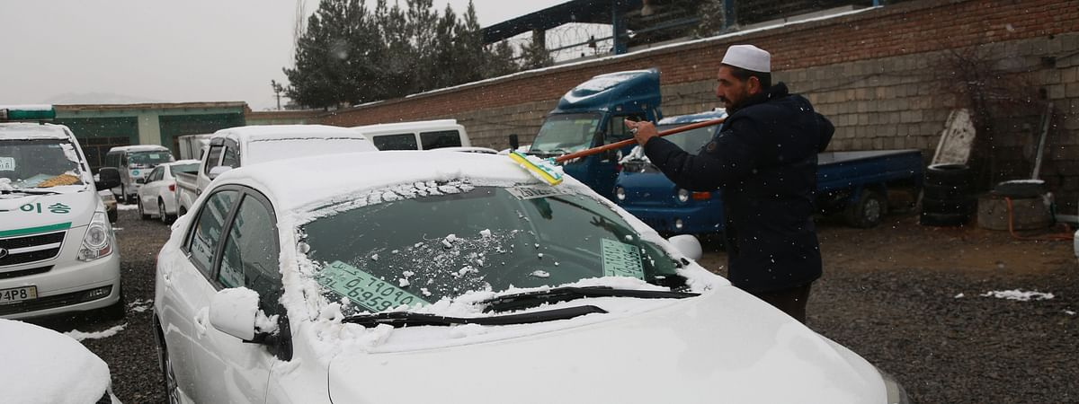 File photo of a man clearing up snow on his car during a snowfall in Kabul, capital of Afghanistan, January 1, 2020, when the city received its first snowfall of the winter.