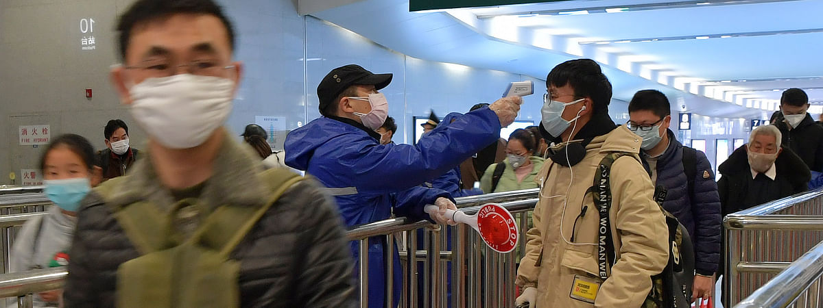 A staff member checks the body temperature of passengers at the Nanchang Railway Station in Nanchang, east China's Jiangxi Province, on February 6, 2020 as part of the measures to curb the spread of the novel coronavirus epidemic in the country.