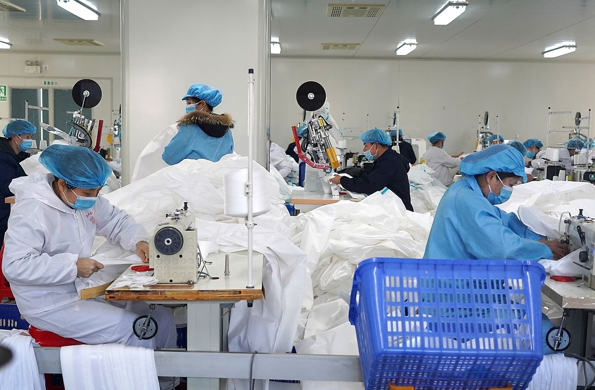 Workers make protective suits at the workshop of a company in Jinxian County, east China's Jiangxi Province, on February 1, 2020 as part of the fight against the novel coronavirus outbreak in the country.