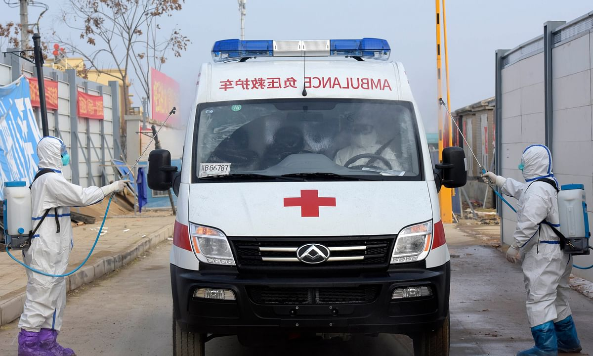 Medical staff disinfect an ambulance carrying cured patients at Huoshenshan Hospital in Wuhan, central China's Hubei Province, on February 13, 2020.