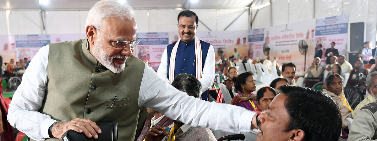 Prime Minister Narendra Modi distributing assistive aids and devices to senior citizens and physically challenged people at a camp at Prayagraj in Uttar Pradesh, on February 29, 2020.