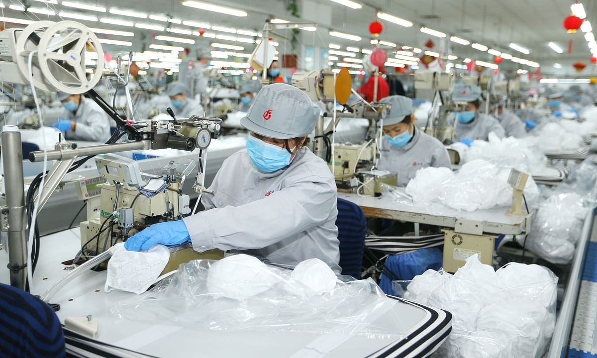 Workers making face masks at a textile company in Qingdao in east China's Shandong province on February 12, 2020, as part of the efforts to combat the novel coronavirus epidemic that has hit the country.