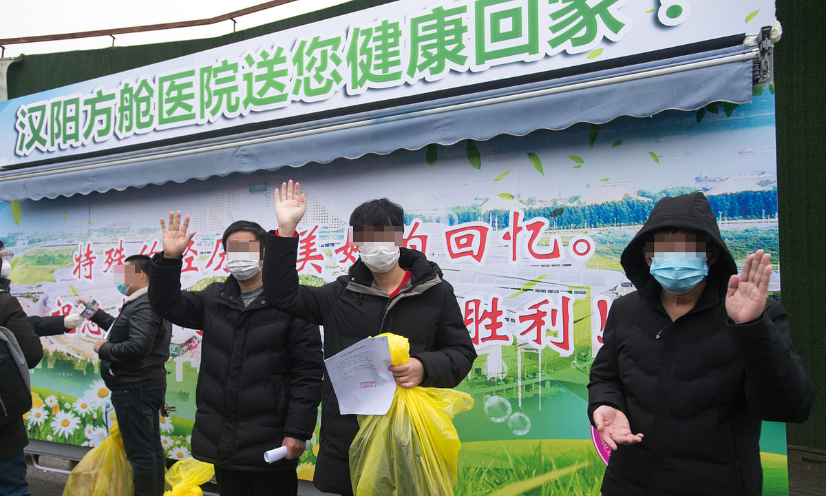 Recovered patients who had been infected with novel coronavirus pneumonia (NCP) wave to medical staff while leaving a temporary hospital in Wuhan, China on February 21, 2020.