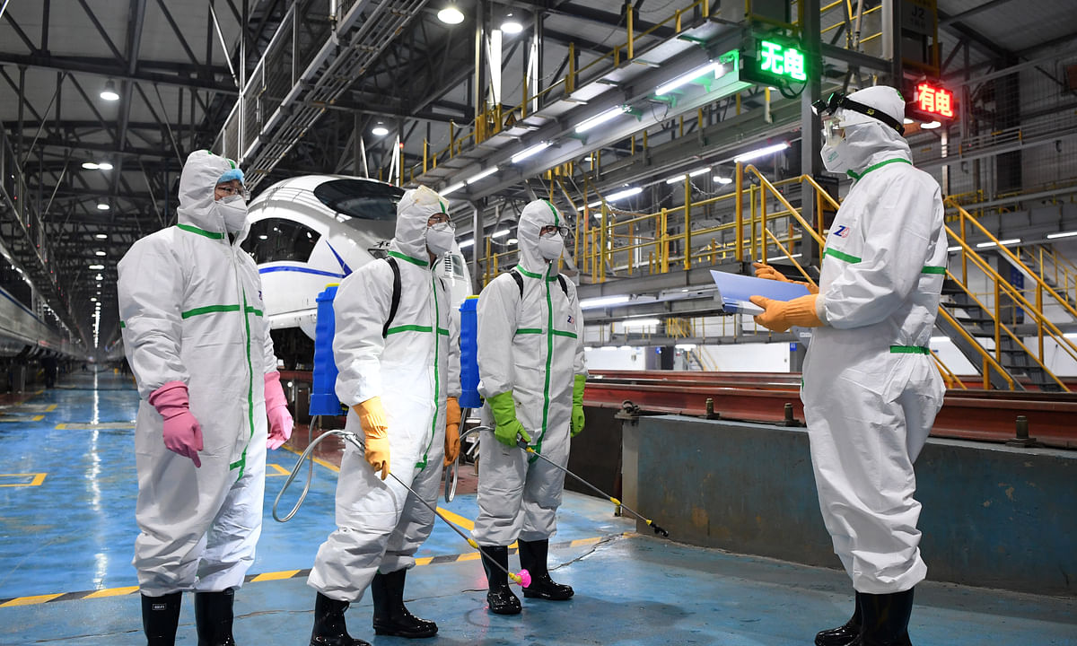 Staff members review progress while disinfecting bullet trains in southwest China's Chongqing Municipality, on February 2, 2020 as part of the efforts to prevent and control the spread of the novel coronavirus that has broken out in the country.