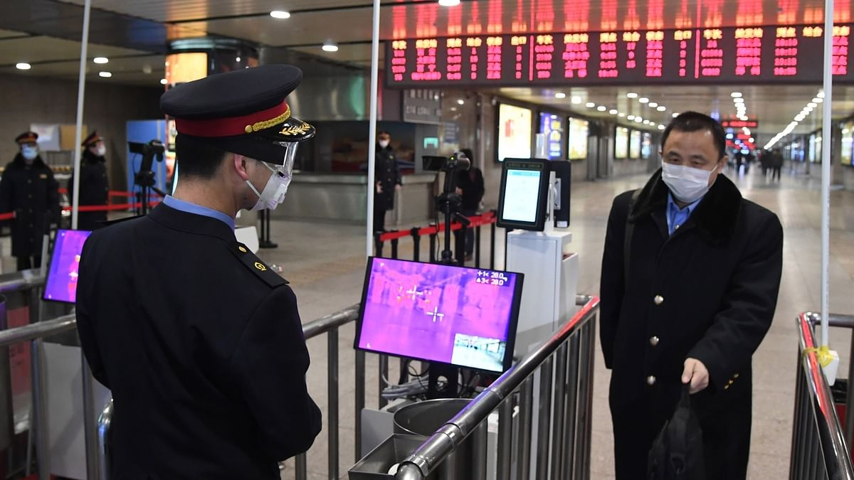 A staff member checks a passenger's temperature at the exit of Beijing West Railway Station in Beijing, capital of China, on February 2, 2020 as part of measures to battle the novel coronavirus epidemic.