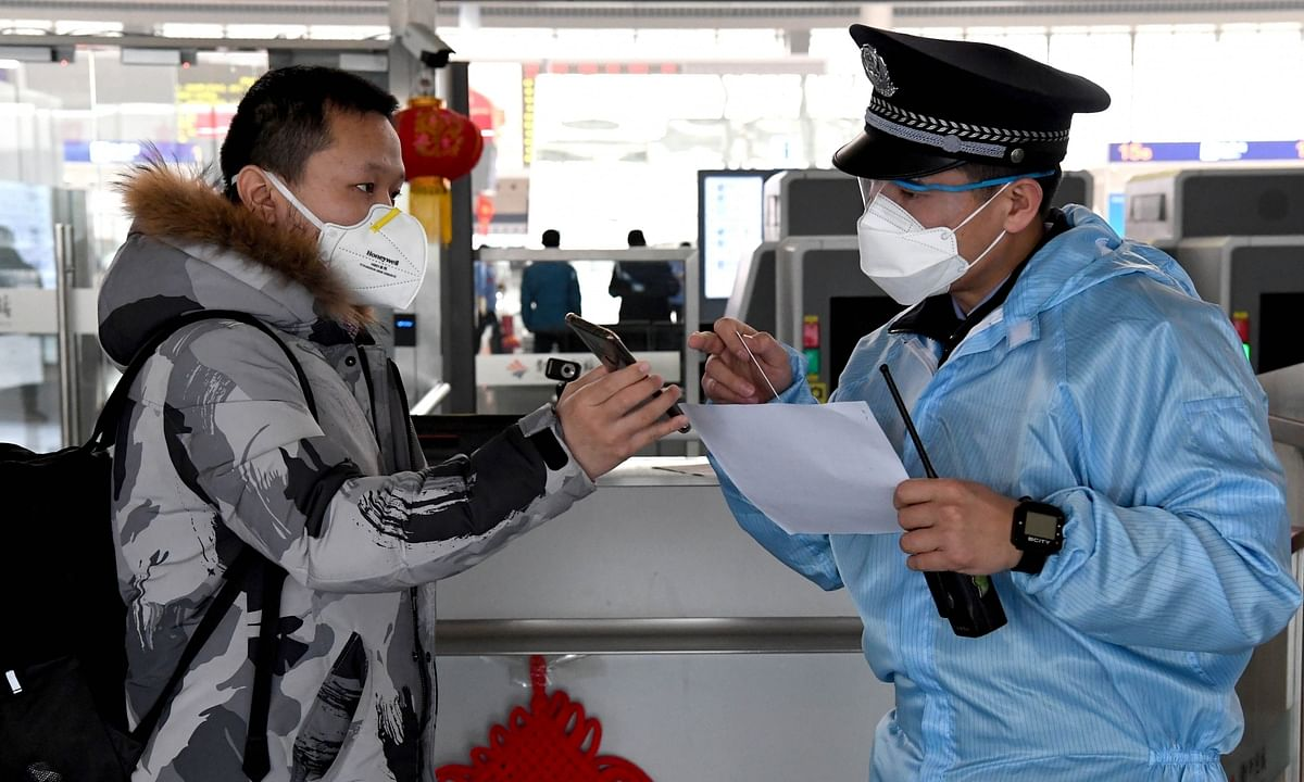 A railway policeman checks a passenger's identity and travel information at Zhengzhou East Railway Station in Zhengzhou, central China's Henan Province, on February 1, 2020, as part of the country's efforts to prevent and control  the spread of novel coronavirus.