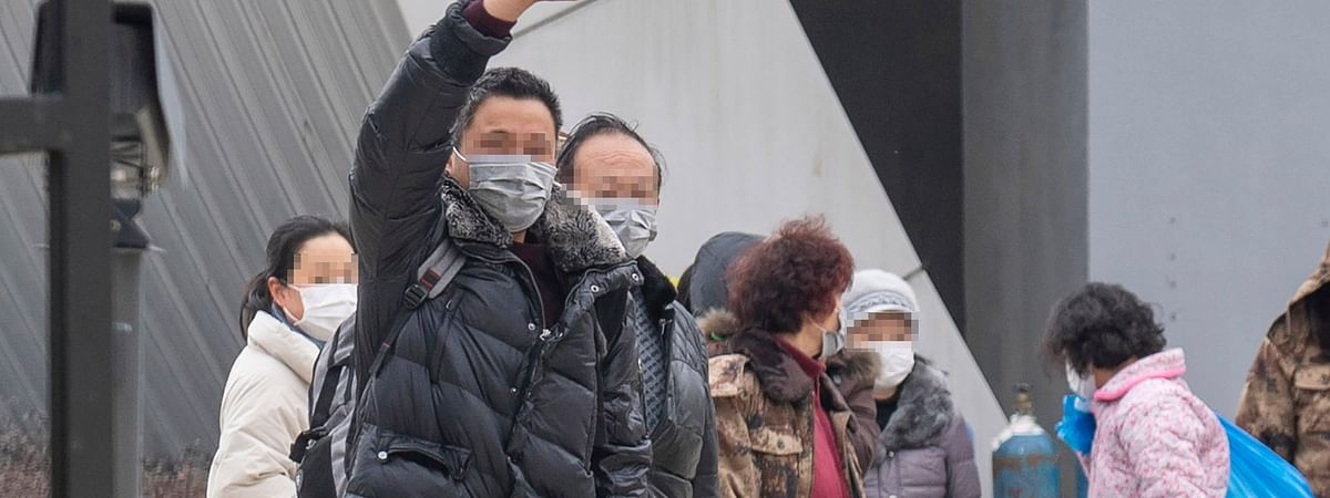 Cured COVID-19 patients are seen leaving a makeshift hospital in Wuhan, central China's Hubei Province, on March 1, 2020.
