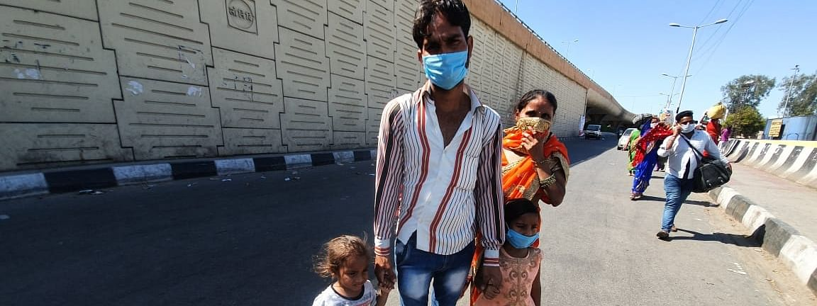 Migrant workers heading back home with their families, at Anand Vihar bus terminal close to Delhi's border with Ghaziabad on Day 5 of the 21-day countrywide lockdown imposed to contain the spread of novel coronavirus, on March 29, 2020.