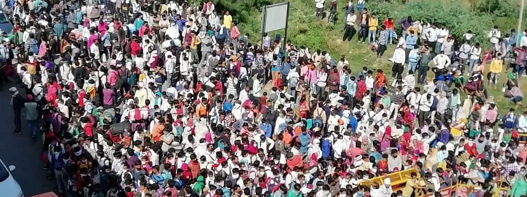 Hundreds of migrant workers waiting at the Delhi border for buses to carry them home in Uttar Pradesh, on March 28, 2020 as the 21-day lockdown to contain the coronavirus has left them without any income, food or shelter.