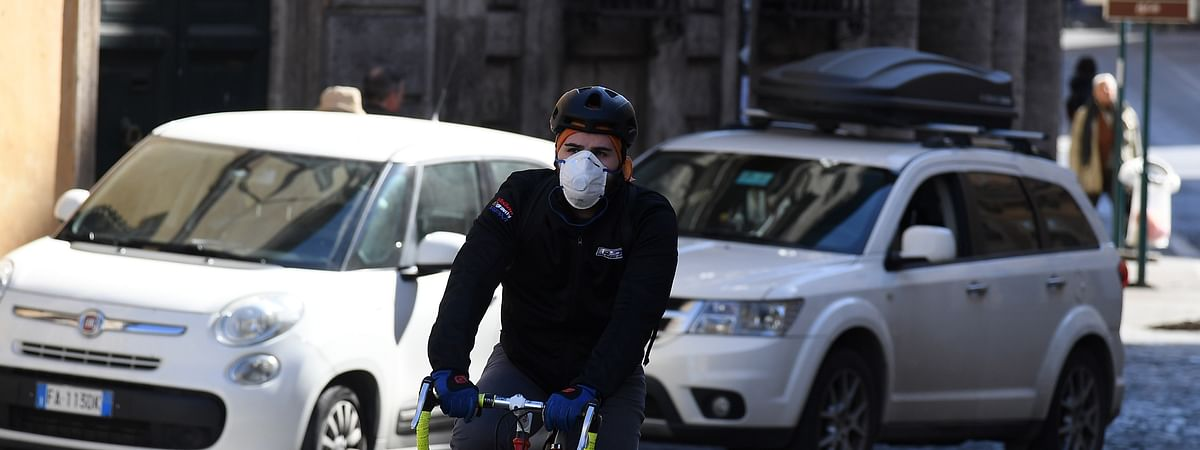 A man wearing a face mask rides a bicycle in Rome, Italy, on March 12, 2020.