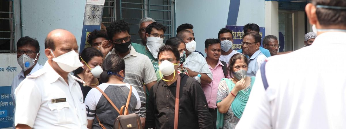 Patients wearing masks waiting outside the Beleghata Infectious Diseases Hospital amid COVID-19 (coronavirus) pandemic, in Kolkata on March 18, 2020.