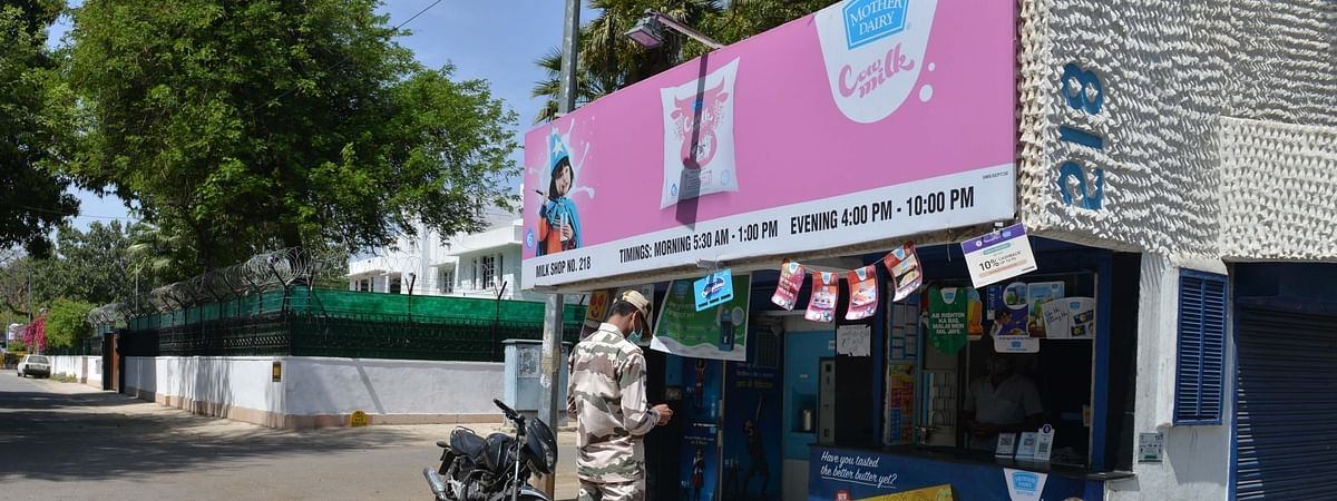 A security personnel stands outside a Mother Dairy booth with the adjoining street marked with chalk for people to practise social distancing during the complete lockdown for 21 days announced by Prime Minister Narendra Modi to prevent further spreading of the COVID-19 pandemic in India; in New Delhi on March 25, 2020.