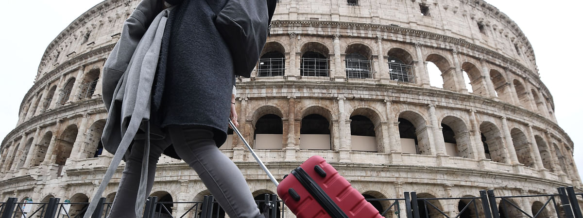 A woman walks past the Colosseum in Rome, Italy, on March 13, 2020.