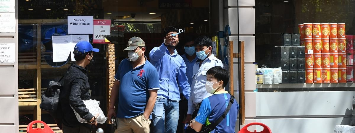 People being provided with hand sanitisers at a supermarket during the complete lockdown for 21 days imposed by the government to contain the spread of COVID-19 in India, in New Delhi on March 25 2020.