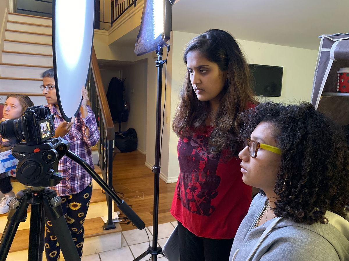 Suresh (red/center right) watching a shot for her upcoming film, Bandaid with cinematographer Alyssa Rivas (far right). Crew members Emily Holshouser (far left) and Aishwarya Kumar (center left) help.