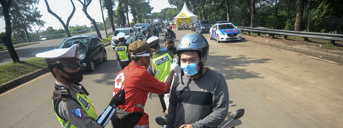 Indonesian police officers check the identity cards of motorcyclists during the implementation of large-scale social restrictions amid the COVID-19 pandemic at South Tangerang in Indonesia, on April 18, 2020.