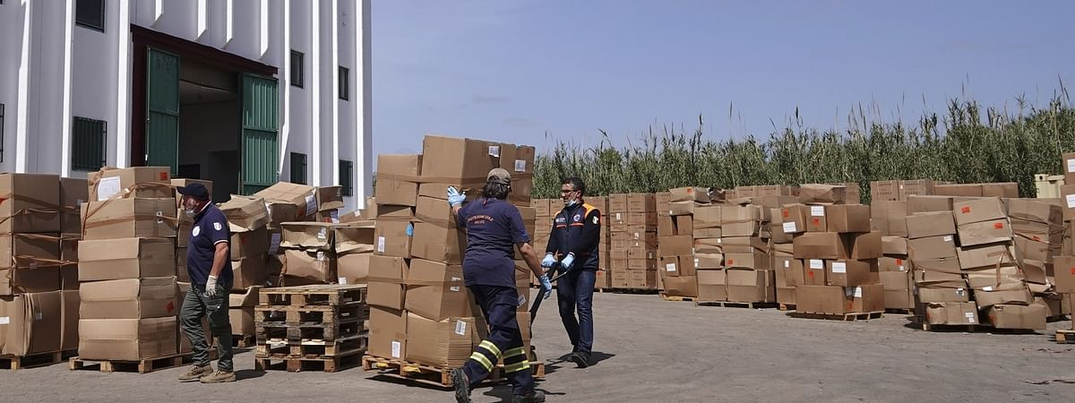 Retired firefighters transfer boxes of medical supplies outside a warehouse near Fiumicino airport in Rome, Italy, on April 17, 2020.
